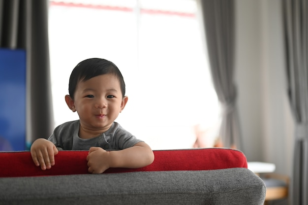 Portret van mooie hppy babyjongen zittend op de bank in comfortabel huis.