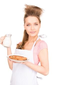 Portret van mooie huisvrouw met melk en koekjes
