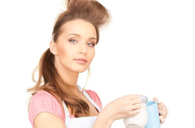 Portret van mooie huisvrouw met melk en mok