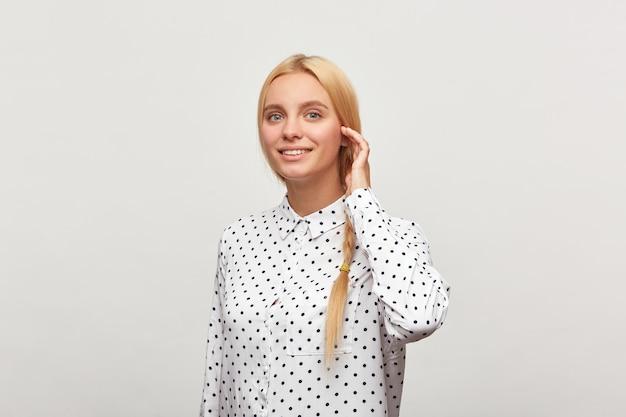 Portret van mooie ijverige blonde vrouw met blauwe ogen, staande in een halve draai corrigeert haar vlecht