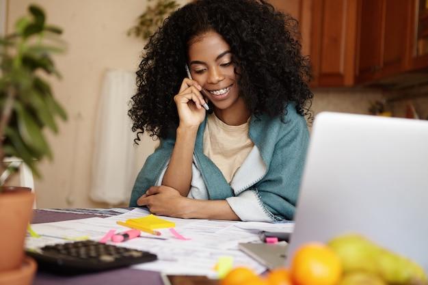 Portret van mooie jonge afrikaanse huisvrouw met bretels glimlachend gelukkig, praten over de telefoon zittend aan de keukentafel met rekenmachine en laptop pc, gezinsbudget beheren en papierwerk doen