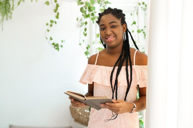 Portret van mooie jonge afrikaanse vrouw in jurk met boek