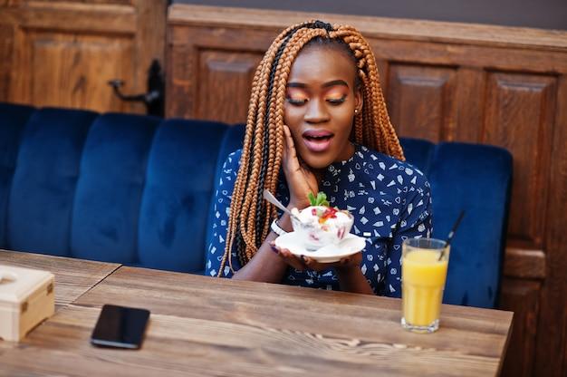 Portret van mooie jonge afrikaanse zakenvrouw met dreadlocks, slijtage op blauwe blouse en rok, zittend in café met ijs en ananassap. verrast gezicht.