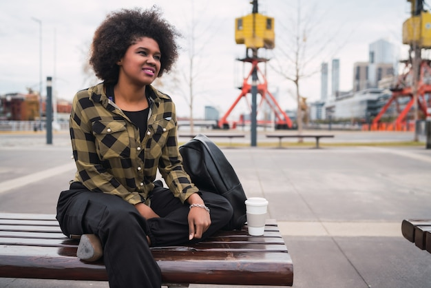 Portret van mooie jonge afro amerikaanse latijns-vrouw met krullend haar buiten zitten in de straat.