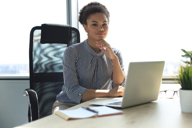 Portret van mooie jonge afro-amerikaanse vrouw die met laptop werkt terwijl ze aan tafel zit.