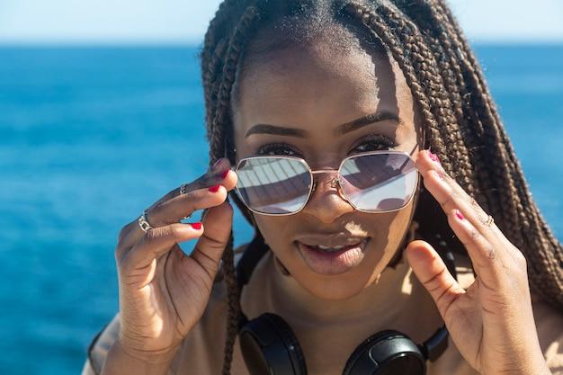 Portret van mooie jonge afro meisje met zonnebril en koptelefoon camera kijken op zee en hemel achtergrond.