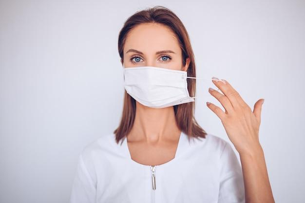 Portret van mooie jonge arts die beschermend masker draagt
