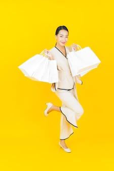 Portret van mooie jonge aziatische bedrijfsvrouw met boodschappentas van warenhuis en wandelgalerij op gele muur