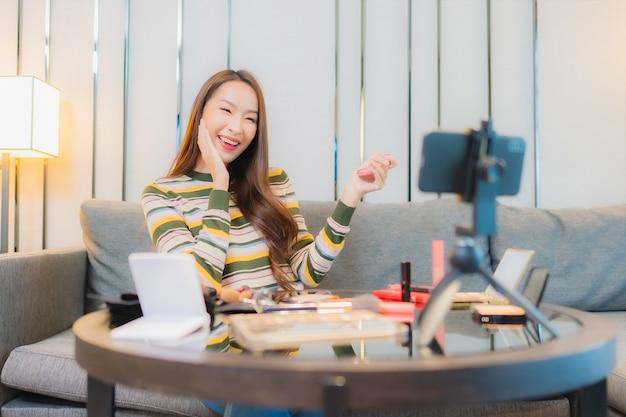 Portret van mooie jonge aziatische vrouw beoordelingen en maakt gebruik van cosmetica op de bank