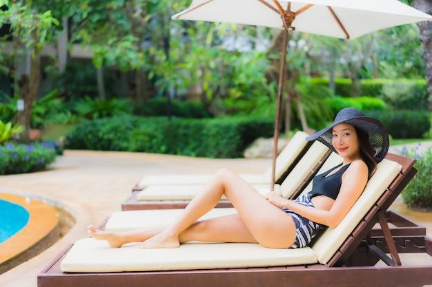 Portret van mooie jonge aziatische vrouw dichtbij het zwembad