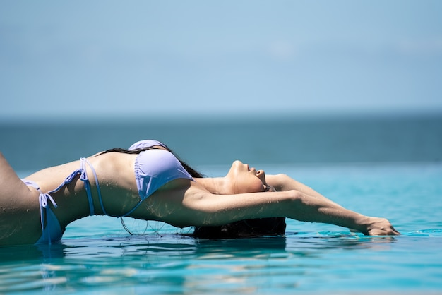 Portret van mooie jonge aziatische vrouw die bikini op het strand draagt
