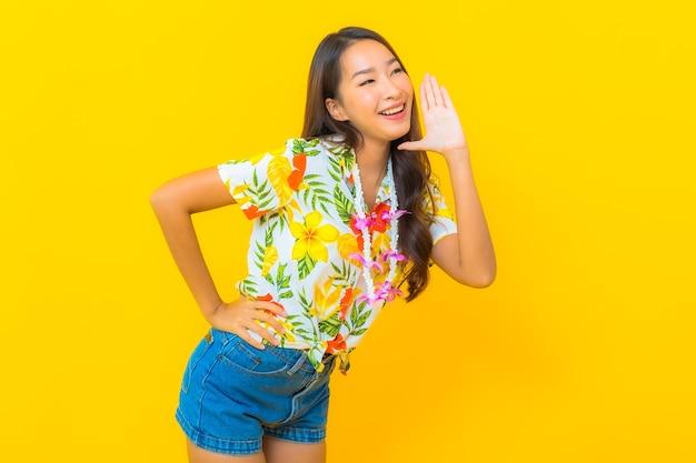 Portret van mooie jonge aziatische vrouw die kleurrijk overhemd draagt en een geheim op gele muur vertelt