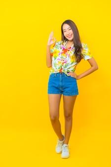 Portret van mooie jonge aziatische vrouw die kleurrijk overhemd draagt en ok teken op gele muur geeft