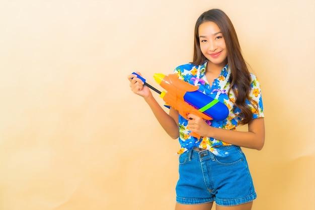 Portret van mooie jonge aziatische vrouw die kleurrijk overhemd draagt en waterpistool houdt