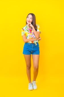 Portret van mooie jonge aziatische vrouw die kleurrijk overhemd op gele muur draagt