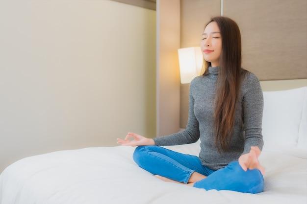 Portret van mooie jonge aziatische vrouw die meditatie op bed doet