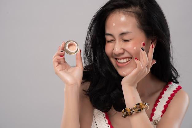 Portret van mooie jonge aziatische vrouw die room op haar gezicht uitspreidt.