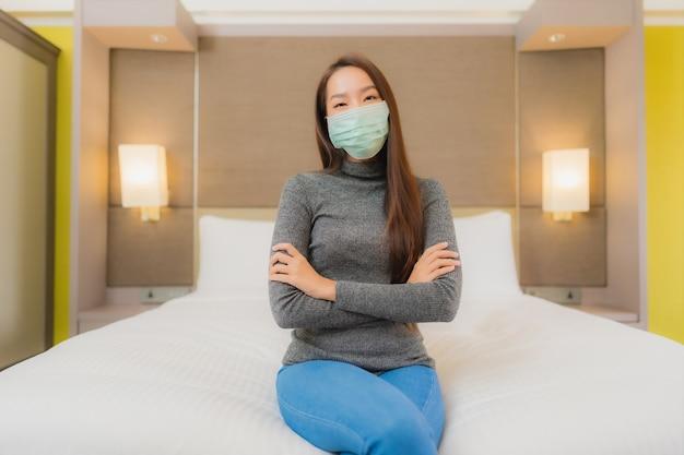Portret van mooie jonge aziatische vrouw draagt masker in slaapkamer