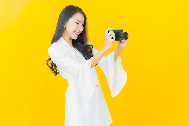 Portret van mooie jonge aziatische vrouw gebruikt camera op gele muur
