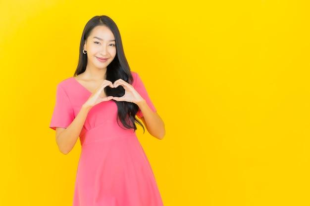 Portret van mooie jonge aziatische vrouw glimlacht in roze jurk doet hartvorm op gele muur