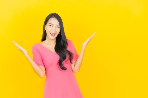 Portret van mooie jonge aziatische vrouw glimlacht in roze jurk op gele muur