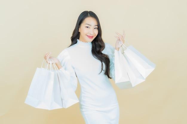 Portret van mooie jonge aziatische vrouw glimlacht met boodschappentas op kleur muur