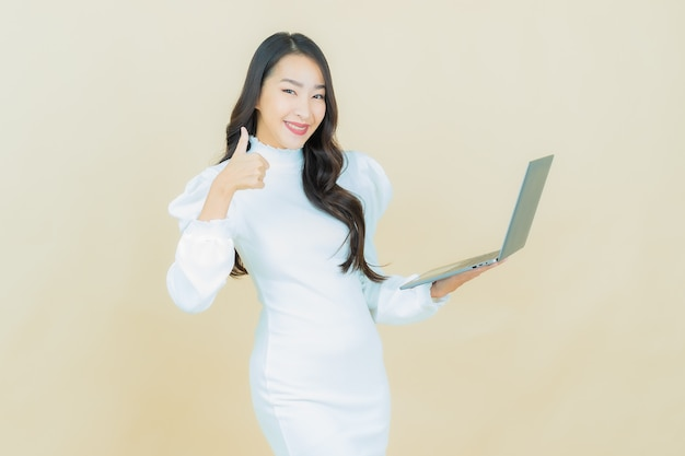 Portret van mooie jonge aziatische vrouw glimlacht met computer laptop op geïsoleerde muur