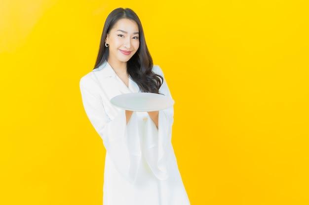 Portret van mooie jonge aziatische vrouw glimlacht met lege bordschotel op gele muur