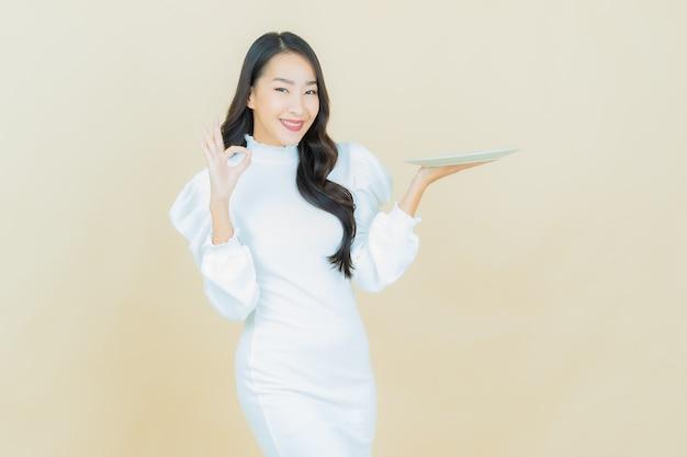 Portret van mooie jonge aziatische vrouw glimlacht met lege bordschotel op kleurenmuur