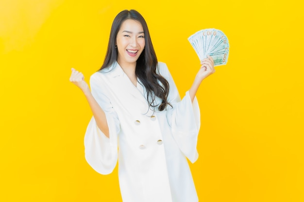 Portret van mooie jonge aziatische vrouw glimlacht met veel contant geld en geld op gele muur