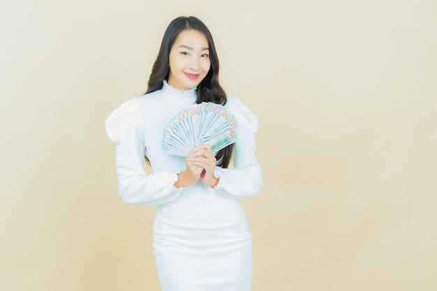 Portret van mooie jonge aziatische vrouw glimlacht met veel contant geld en geld op kleurenmuur
