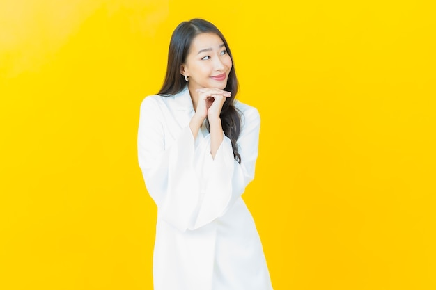 Portret van mooie jonge aziatische vrouw glimlacht op gele muur