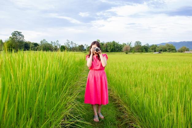Portret van mooie jonge aziatische vrouw in uitstekende roze kleding die een foto nemen