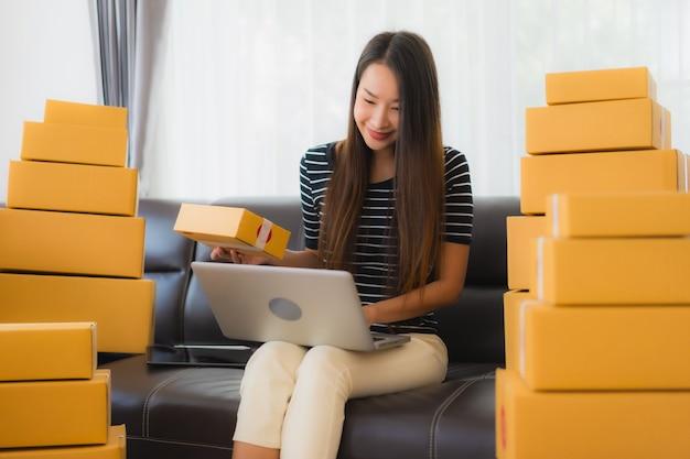 Portret van mooie jonge aziatische vrouw met kartonnen pakket dozen en laptop