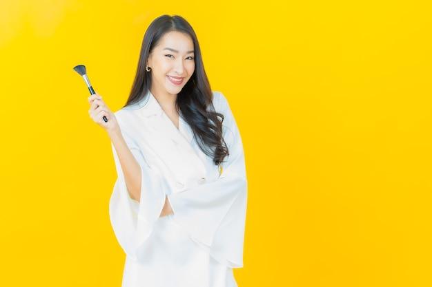 Portret van mooie jonge aziatische vrouw met make-up borstel cosmetica op gele muur