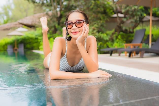 Portret van mooie jonge aziatische vrouw ontspannen rond buitenzwembad in hotel resort bijna zee