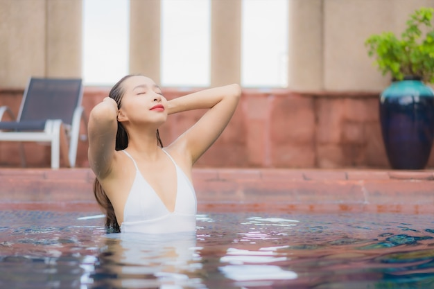 Portret van mooie jonge aziatische vrouw ontspant in het zwembad