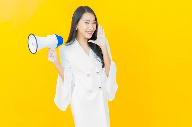 Portret van mooie jonge aziatische vrouwenglimlach met megafoon op gele muur