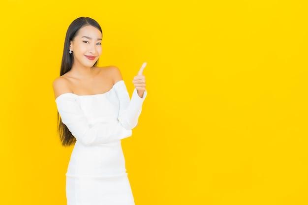 Portret van mooie jonge bedrijfs aziatische vrouw die en duimen met witte kleding op gele muur glimlacht opgeeft