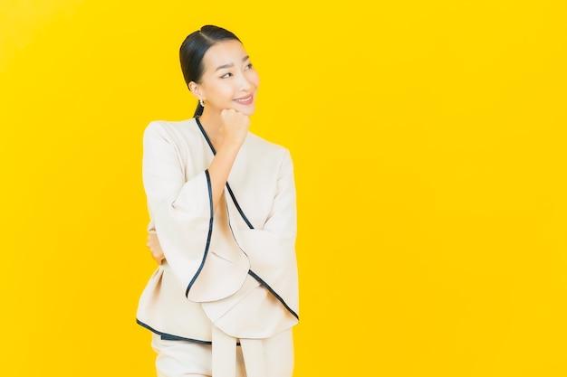 Portret van mooie jonge bedrijfs aziatische vrouw die met wit kostuum op gele muur glimlacht