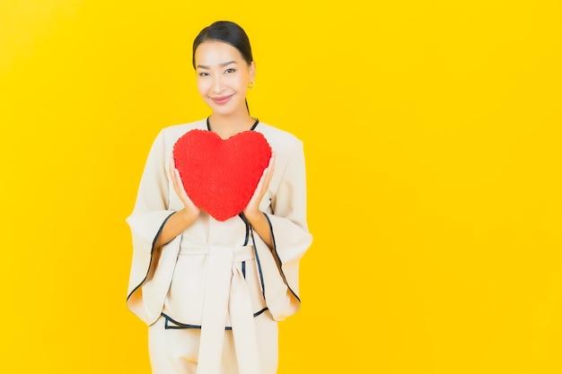 Portret van mooie jonge bedrijfs aziatische vrouw met hartvormig hoofdkussen op gele kleurenmuur