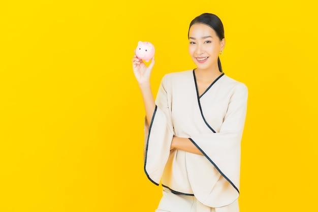 Portret van mooie jonge bedrijfs aziatische vrouw met heel wat contant geld en spaarvarken op gele muur