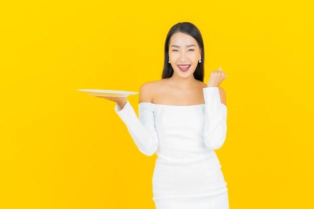 Portret van mooie jonge bedrijfs aziatische vrouw met lege schotelplaat op gele muur