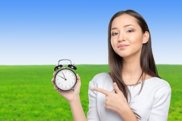 Portret van mooie jonge bedrijfsvrouw die een klok houdt