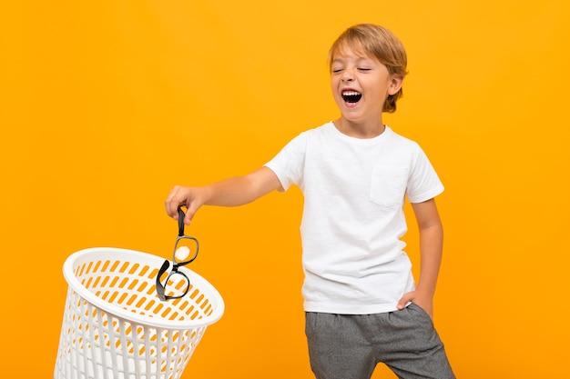 Portret van mooie jonge blanke jongen in wit t-shirt en grijze broek glimlacht en gooit zijn bril weg