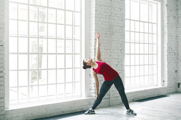 Portret van mooie jonge blanke vrouw in trendy sportkleding trainen in ruime lichte kamer door grote ramen, zijwaartse buiging oefening doen. yoga, fitness, sport en een gezonde levensstijl