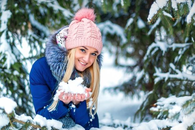 Portret van mooie jonge blanke vrouw met sneeuw in haar handen