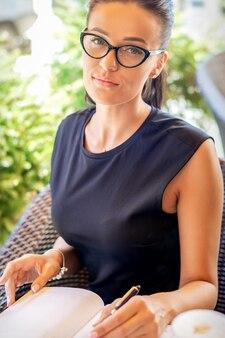 Portret van mooie jonge blanke zakenvrouw maakt aantekeningen op notebook met bril in café