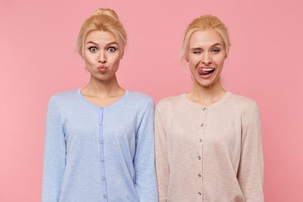Portret van mooie jonge blonde tweeling gek rond en maakt gezichten geïsoleerd op roze achtergrond. het ene meisje stuurt een kus en het tweede meisje tongent tand en knipoogt.