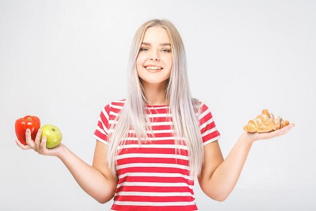 Portret van mooie jonge blonde vrouw die tussen gezond en ongezond voedsel kiest. geïsoleerd op witte achtergrond.